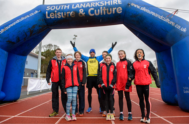 Captions: 401 marathon man Ben Smith with young members of the Law and District AAC who accompanied him on the last leg as he entered Carluke's John Cumming stadium at the end of his 208th marathon