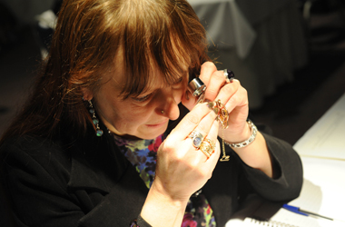 antiques expert examining piece of jewellery