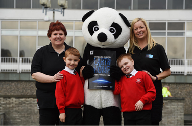Big Sing in the Dark - Laura Gaddis, South Lanarkshire staff choir joined by pupils from East Milton primary school, the WWF panda and the council's Sustainable Development Officer Lesley Hinshelwood