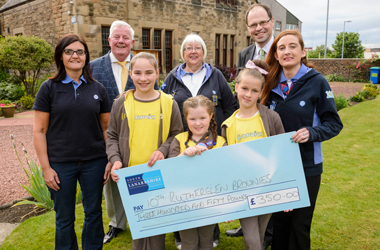 Councillors Russell Clearie and Richard Tullett present a Community Grant cheque to Irene Laird (centre, back), Unit Leader of 10th Rutherglen Brownies, with some of the Brownies and young leaders