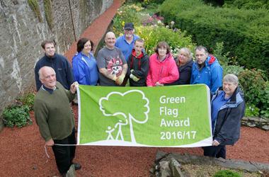 volunteers holding up the Green Flag banner in Castlebank Park, Lanark