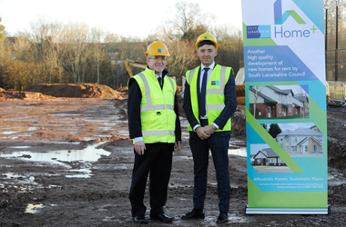 Daniel Lowe and Councillor Wilson next to Home+ advertising in building site