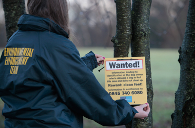 environmental enforcement officer erecting 'Wanted' dog fouling notice