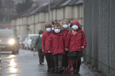 children with masks over their mouths to protect their lungs from exhaust emmissions from idling cars