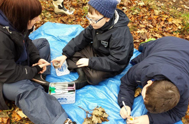 Forest school teacher with two primary pupils