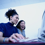 An instructor helps a woman at a computer