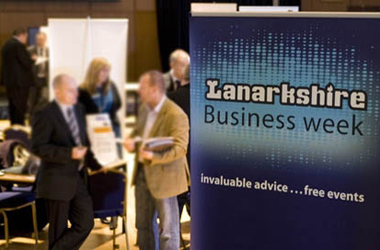 Lanarkshire Business Week event with atendees in background behind business week poster