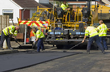 Road workers resurfacing road