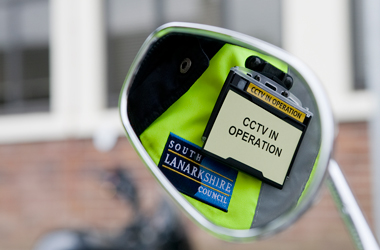 driving mirror showing parking attendant uniform with CCTV notice
