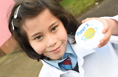 St Vincent's Primary School pupil with badge created as part of 'NASA' project - Our Fragile Earth - about humans moving to another planet