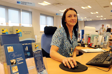 customer service staff at desk with Q&A leaflets