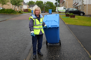 council staff with blue recycling bin at kerb-side