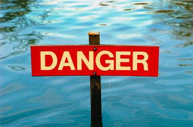 danger sign in front of flooded road