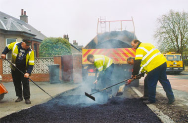 workers resurfacing road