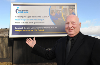 Council Leader eddie McAvoy next to hoarding advertising freephone number to help unemployed people in South Lanarkshire back into work