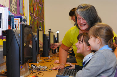 Pupils and teacher looking at computer