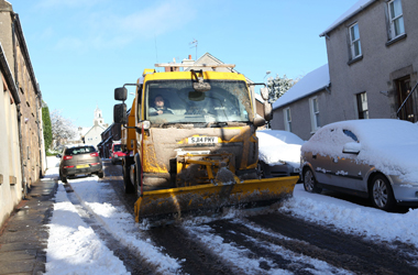 snow cleared from footpath with snow plow and gritting of secondary route