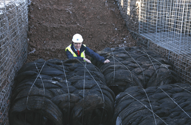 Councillor Graham Simpson, the Depute Chair of the council's Enterprise Resources Committee with the tyre bails used to replace peat layer in country road