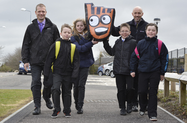 photo shows Chair of council's Road Safety Forum Councillor Graham Simpson with Chris Thompson, schools co-ordinator for Living Streets Scotland and High Mill Primary pupils holding aloft Strider, Living Streets Road Safety mascot