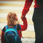 parent holding child's hand on way into school