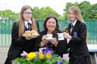 Marie Watters being served vintage afternoon tea in the Holy Cross roof garden by two of this year's kickstart group
