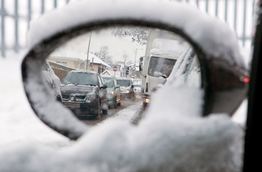 snow on car side mirror with congested traffic in view