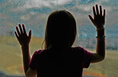 child looking out a window with arms outstretched