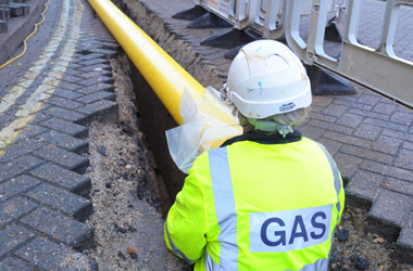gas worker laying new yellow pipe